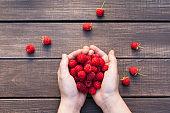 Fresh raspberries in woman's hands on wood background