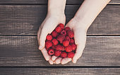 Fresh raspberries in woman's hands on wood background