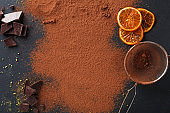 Cocoa powder in a sieve over black slate background