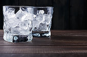 Glasses with ice cubes on dark background
