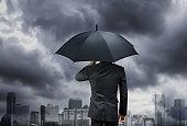 businessman hold umbrella under rain storm with city background