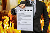 businessman show home insurance policy with fire
