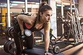 Sporty young woman lifting weights at gym.