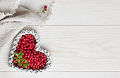 Fresh red forest berries in the shape of heart on a white wooden background.