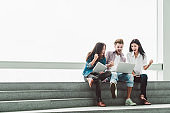 Multiethnic group of college students or freelance coworkers celebrate together with laptop and tablet. Creative team or business colleague at modern office. Startup, teamwork, success project concept