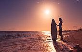Woman surfer at sunset beach