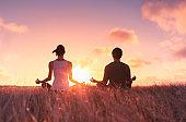 Couple meditating at sunset