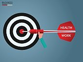 Goal setting. Hand holding dart with text ' Health, Work' to target. Concept of work and life balance.