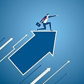 Businessman on growth arrow graph pointing finger and looking for success, opportunities, future business trends. Vision concept.