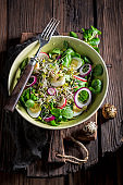 Spring green salad with lettuce, arugula and quail egg
