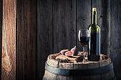 Red wine with figs on oak barrel