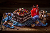 Delicious chocolate cake with walnuts and cherry