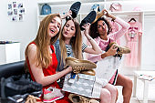 Positive teen girlfriends having fun time together while doing shopping sitting choosing new shoes fooling around and making faces in clothing shop