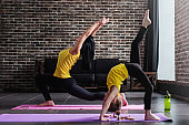 Young female adult doing crescent lunge pose and girl child standing in one-legged inverted staff position during yoga training in stylish loft studio