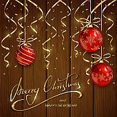 Christmas and New Years lettering with red balls and golden streamers on wooden background