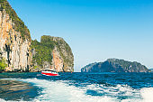 beautiful seascape of rocky mountain and turquoise sea with speed boat at bali island