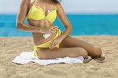 Sexy woman applying suncream at a beach
