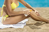 Woman applying sun protection cream at beach