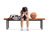 Sad little basketball player sitting on a bench and crying