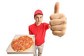 Teenage pizza delivery boy holding a pizza and making a thumb up gesture