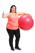 Overweight woman holding pilates ball and making thumb up sign
