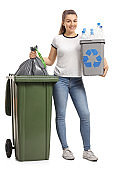 Young girl with a recycling bin and a garbage bag