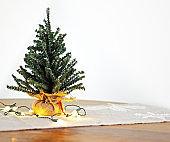 Mini Christmas tree with lights on seasonal table runner