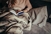 Woman on bed reading book and drinking coffee