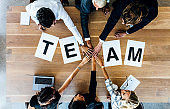 Team word on table with business people stacking hands