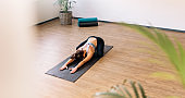 Healthy woman exercising on yoga mat indoors