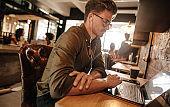 Young man sitting at startup using laptop