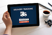 Hand holding tablet with delivery tracking concept on screen