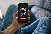 Girl holding smart phone with Black Friday concept on screen