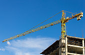 Tower Crane and Skyscraper on Blue Sky Background
