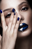Beautiful girl with art make-up, dark glitter lips design and manicured nails. beauty face.