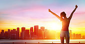 Jogging Fitness And Success - Girl With Arms Raised And Cityscape At Sunset