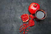 Pomegranate juice and seeds close-up on dark concrete background