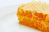 Honeycomb with honey on plate isolated white background