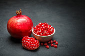 Pomegranate and seeds close-up on dark concrete background