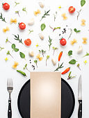 Assorted herb and vegetables and eating utensil on white background.