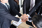 Asian business people joining hands with colleagues together at meeting time for develop job to success, business colleagues teamwork concept
