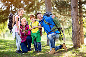 smiling family on hiking shows with finger destination