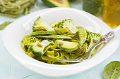 Healthy spinach pasta with broccoli, avocado, pumpkin seeds and green peas.