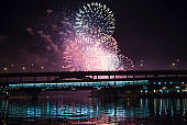Firework over Moscow --  Moskva River, Luzhnetskaya Bridge (Metro Bridge) in the light of night colored lights. Moscow, Russia
