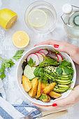 Green healthy vegan breakfast salad with baked potato, avocado and radish