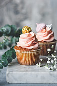 Cupcakes with coral cream and golden decorations on a marble board table.