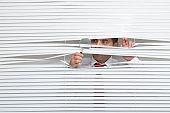 Man Watching through window blinds