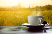 hot coffee on wooden table  meadows background at sunrise