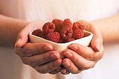 Crockery with raspberries in woman hands