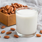 Almond milk in glass with almonds on background, square format